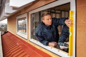 Handwerker nimmt eine Fenstermontage und misst mit Wasserwaage, ob das Fenster gerade eingebaut ist.