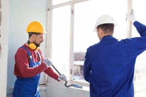 Zwei Handwerker bauen ein Fenster mit Nageleisen aus