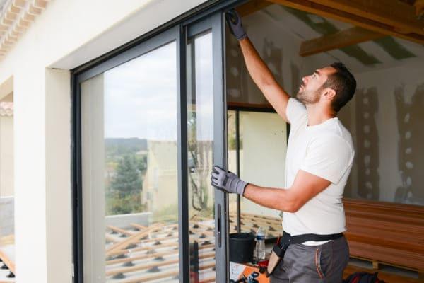 Mann beim Einbau einer Hebeschiebetuer der bei der Fenstermontage einiges beachtet.