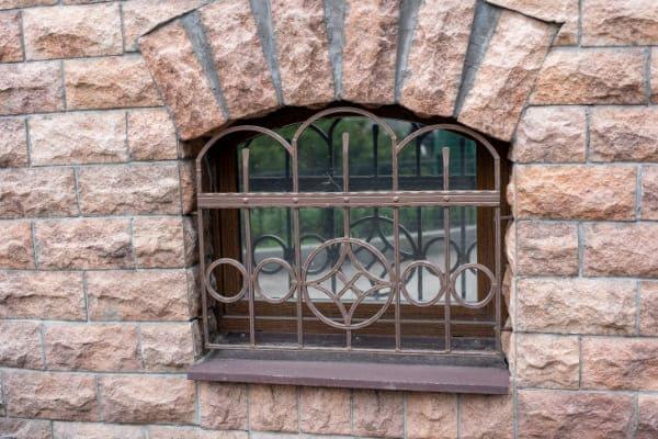 Kellerfenster mit Gitter an Straße.
