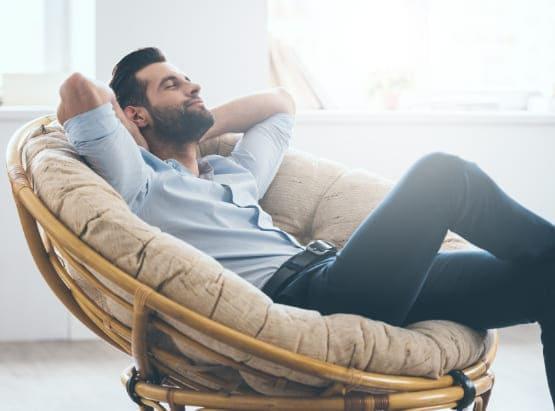 Mann sitzt entspannt in Sessel und genießt den erhöhten Komfort durch Schallschutzfenster.