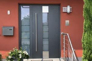 Referenz der Haustür in anthrazit aus Aluminium und Kunststoff an einer roten Hauswand.