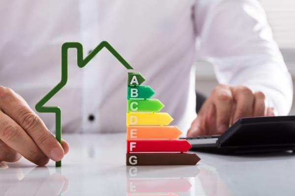 Mann senkt Energiekosten durch Fensteraustausch für sein Haus und stapelt Geld Münzen symbolisch für Geld sparen.