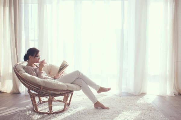 Frau sitzt vor hellem Wohnzimmerfenster und genießt ein Buch und einen Tee