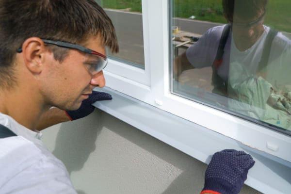 Mann montiert eine Fensterbank unter neues Fenster von Fensterhandel.de