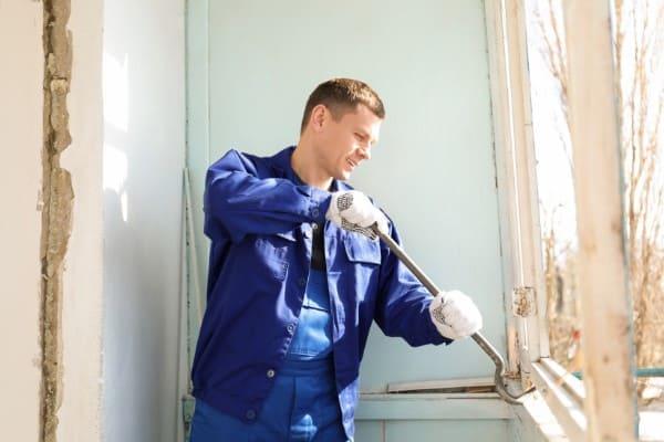 Mann baut den Fensterrahmen ein Holzfensters mit einem Brecheisen aus