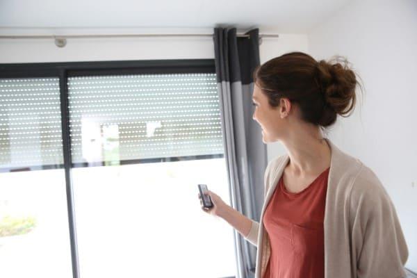 Frau bedient mit Funk-Handsender ein Rollladen, welcher sich komfortabel steuern lässt.