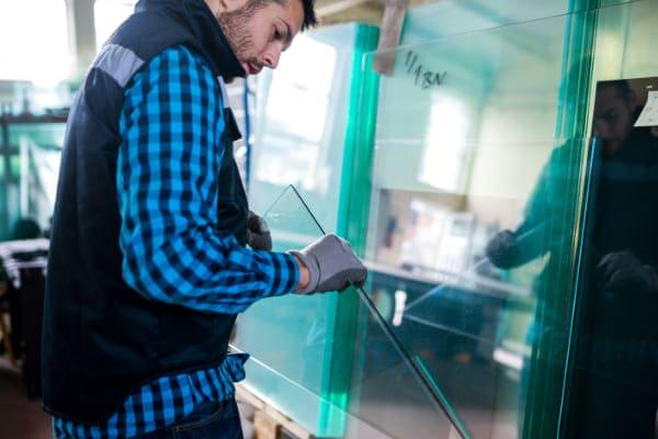 Mitarbeiter eines Glasschieben Herstellers prüft eine Sicherheitsscheibe gewissenhaft