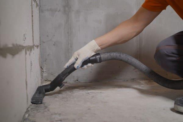 Mann saugt mit Staubsauger für einen sauberen Arbeitsbereich beim Fenstereinbau.