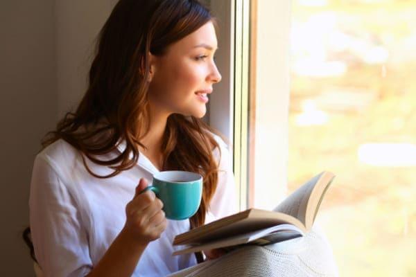 Frau mit Tee und Buch sitzt auf der Fensterbank eines wärmedämmenden Aluminiumfensters und schaut hinaus.