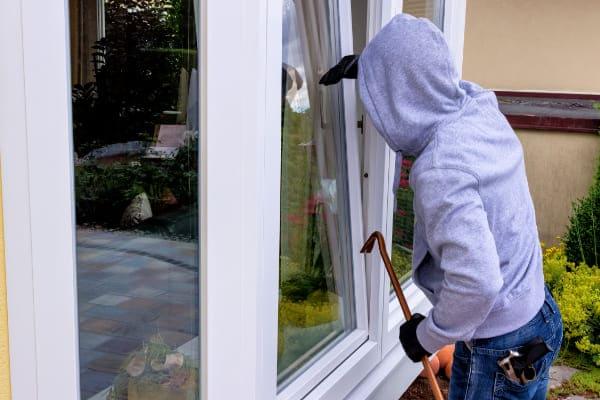 Einbrecher schaut durch gekipptes Fenster