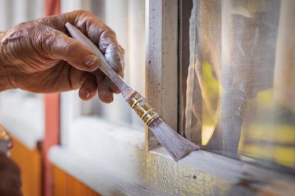 Hand mit Pinsel streicht Holz Fenster und sollte es durch Kunststofffenster ersetzen.