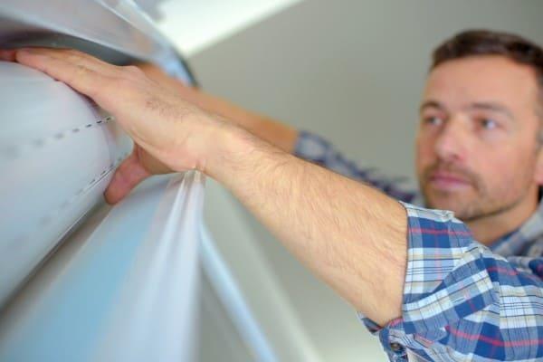 Mann prueft Rollladen innerhalb des Rollladenkastens vor dem Fensterausbau