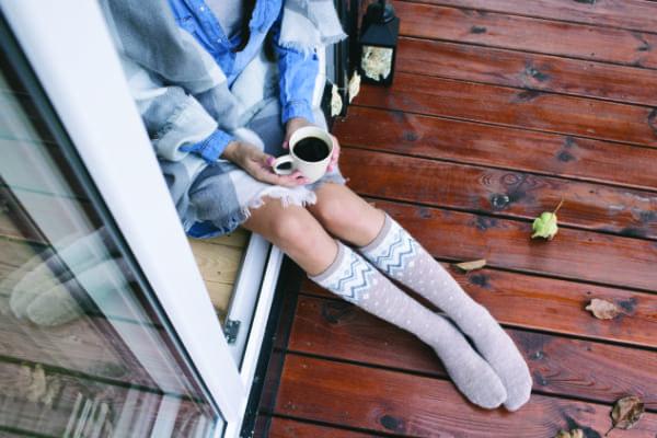 Frau mit Tasse Kaffee bei kaltem Wetter zeigt die Wichtigkeit des U-Werts bei Balkontüren.