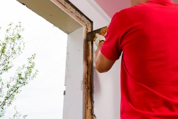 Fensterrahmen wird seitlich mit einer Handsäge herausgesägt.
