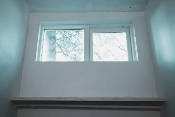Kellerfenster mit Isolierverglasung im Winter.