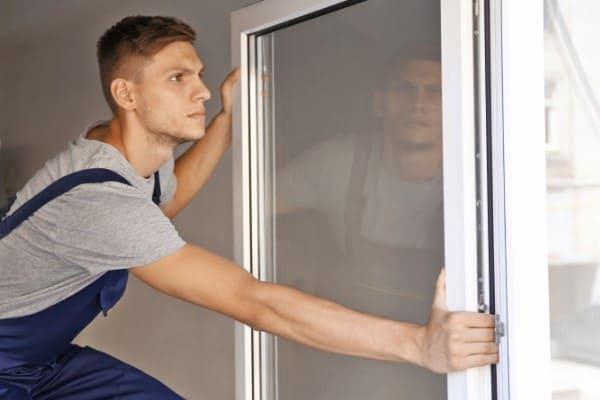 Mann mittelt ein schiefes Fenster gerade