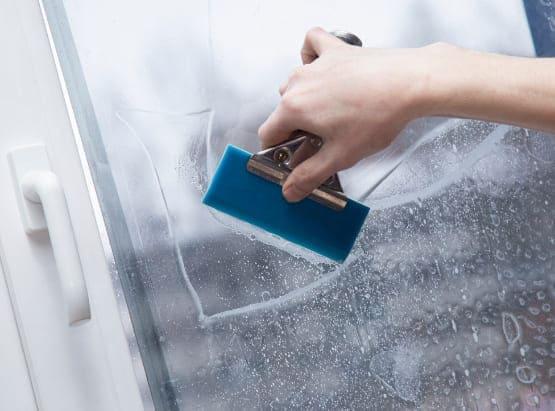 Schallschutzfolie wird mit Fensterschaber aus Kunststoff aufgebracht.