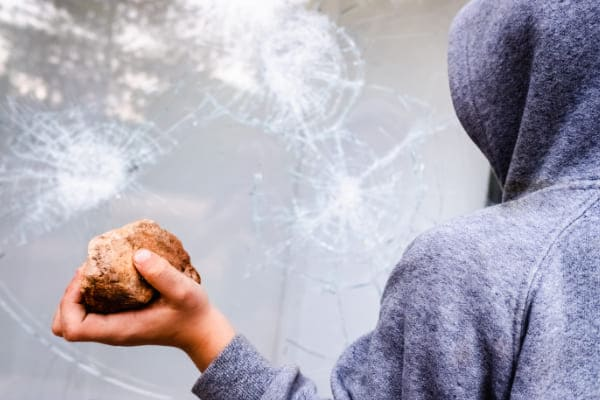 Mann hält Stein in der Hand und wird ihn auf die Scheibe des Aluminiumfensters werfen, welche aber nicht bricht, wegen des Einbruchschutzes.