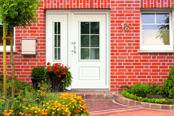 Altmodische Haustüre in Backsteinhaus mit Seitenteil und Glasscheibe als Fenster durchsichtig.