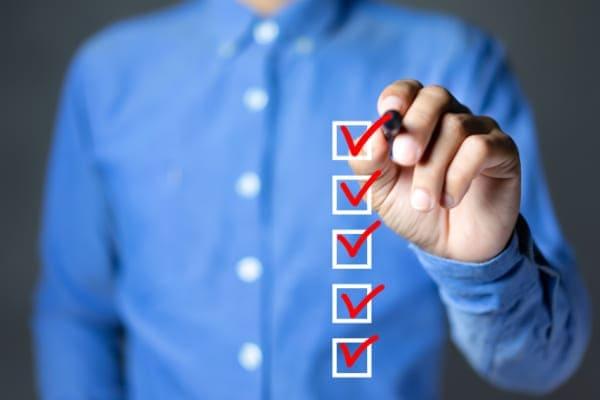 Mann hakt Liste mit zusätzlichen Eigenschaften für Sicherheit bei Aluminiumfenstern ab.