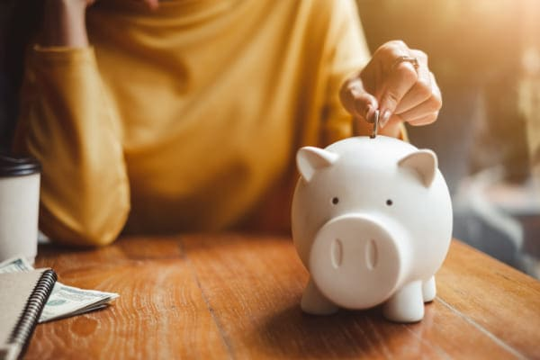 Förderung Fenstertausch, Frau wirft Geld in Sparschwein