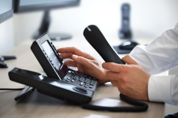 Kundenservice nimmt Hörer in die Hand und wählt mit der anderen um einen Kunden bzgl. PVC Fenster zu beraten.