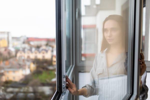Frau bedient auf komfortable Weise ein Fenster aus Aluminium.