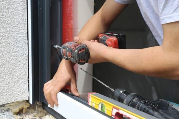 Der Fensterrahmen wird mit einem Akkuschrauber seitlich im Mauerwerk festgeschraubt.