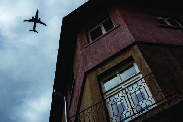 Flugzeug am Himmel bei einer Balkontür macht die Dringlichkeit von Schallschutz deutlich.