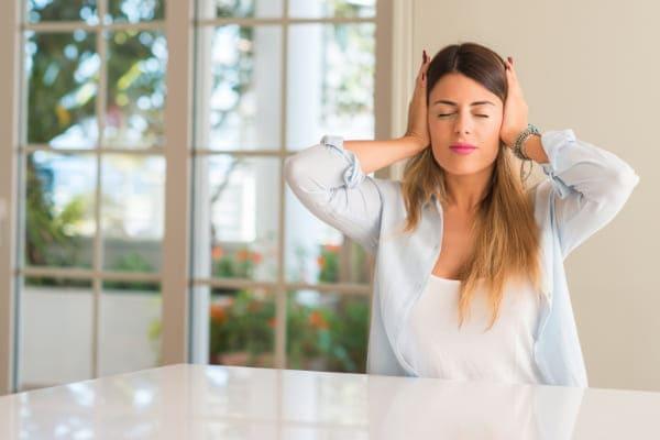 Junge Frau hält sich wegen Schallbelastung die Ohren zu