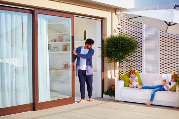 Mann stellt seiner Familie Besonderheiten des Terrassenfensters vor.
