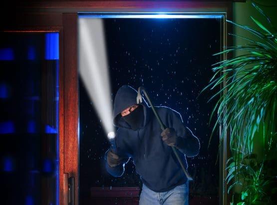 Einbrecher leuchtet in Haus und beachtet das Sicherheitszubehör.