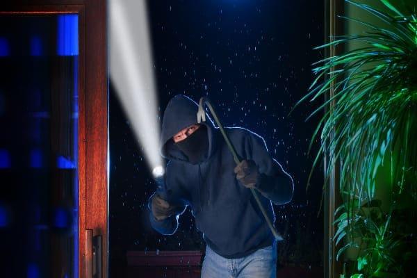 Einbrecher steht vor Terrassenfenster.