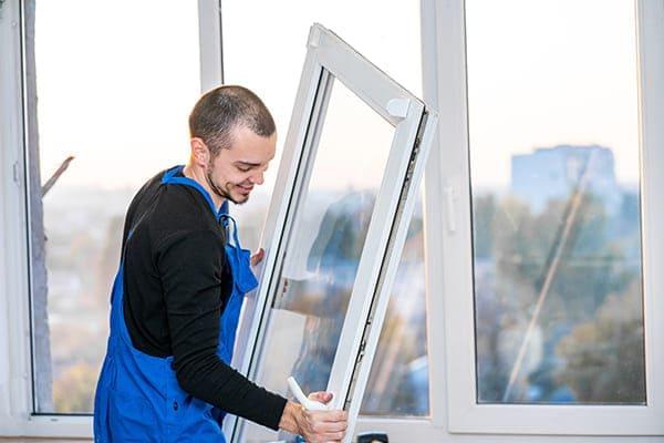 Montuer hält Fensterflügel in der Hand und setzt es ein.