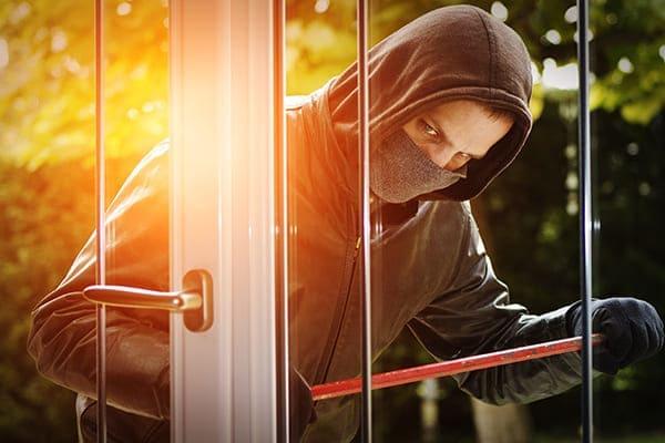 Einbrecher steht für Balkontür und versucht mit einem Brecheisen das Fenster zu öffenen.