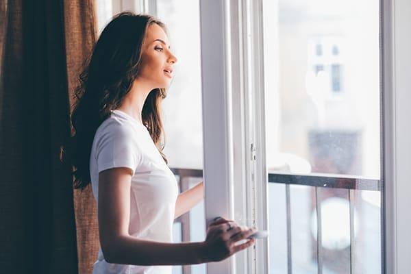 Frau schaut aus geöffneten Balkontür raus.