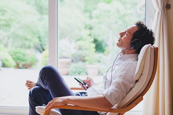 Mann sitzt mit Kopfhörer im Stuhl und hört Musik. Große Balkontür im Hintergrund.