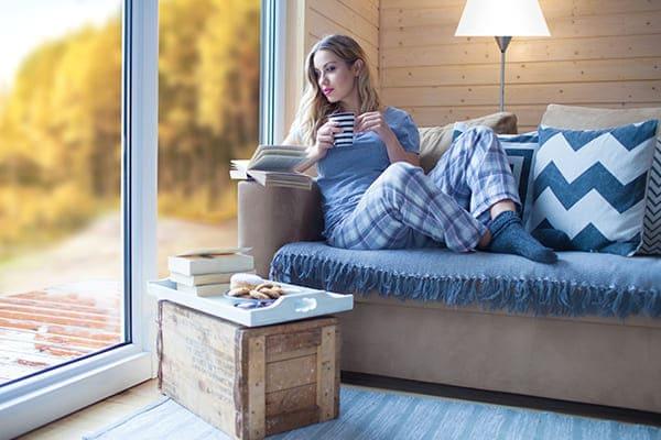Frau sitzt auf Couch und trinkt eine Tasse Tee und schaut dabei aus dem Fenster in eine Winterlandschaft.