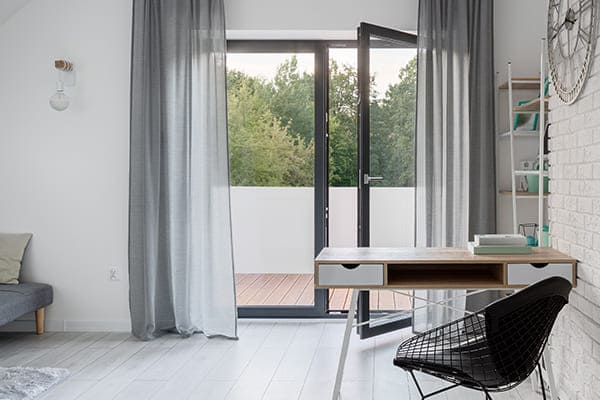 Helles Wohnzimmer mit offener Balkontür.