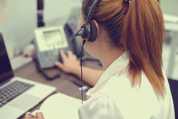 Frau mit Headset Laptop und Telefon im Hintergrund