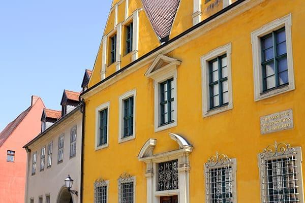 Gelbes Haus von außen mit Denkmalschutzfenster.