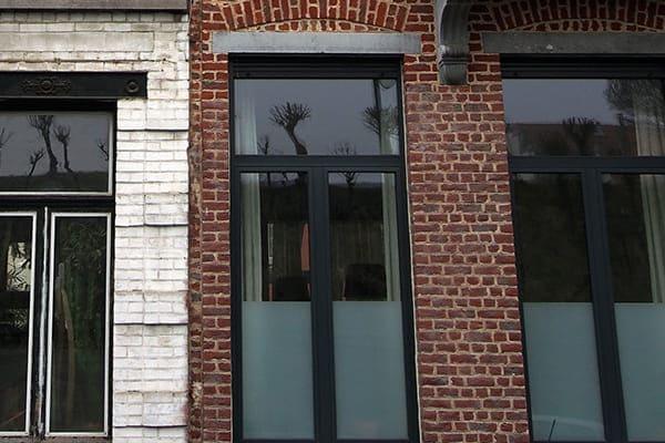 Denkmalschutzgebäude mit neuen Fenstern aus Kunststoff mit Aluminiumschale außen. Links sieht man noch ein Denkmalschutzgebäude mit alten Fenstern aus Holz.