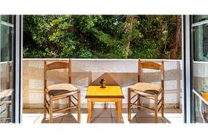 Fensterflügel sind offen mit Blick auf den Balkon mit einem schönen Frühstückstisch und zwei Stühlen.