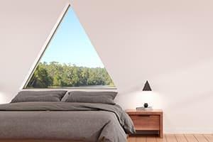 Schönes helles Schlafzimmer mit großem Dreiecksfenster hinter dem Bett.