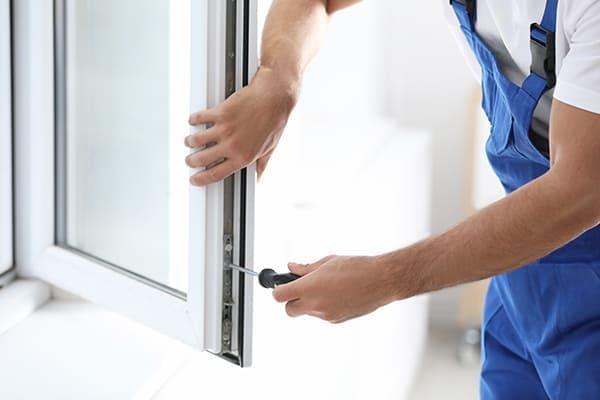 Fenstermonteur stellt Fensterbeschlag ein.