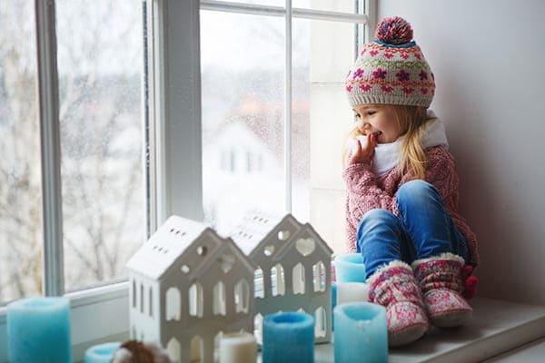 Kleines Mädchen sitzt auf der Fensterbank und sieht aus dem Fenster.