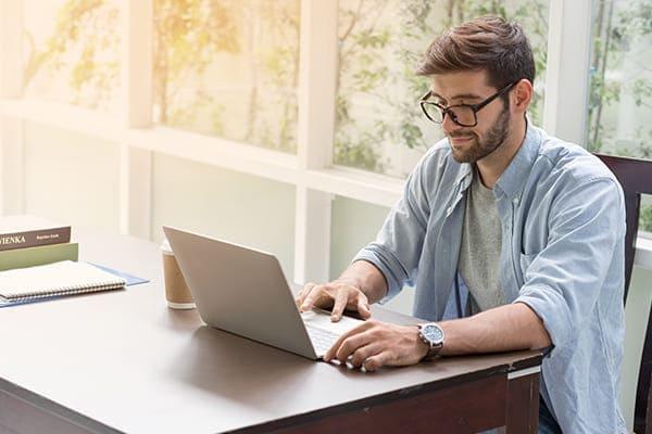 Mann sitz am Leptop und rechnet bei FensterHandel.de Fensterpreise im Online-Konfigurator.