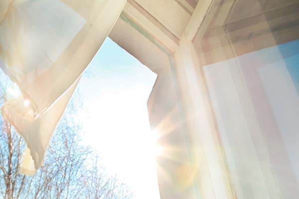 Fenster ist mit offenen Winden bedeckt und strahlt die Vorhangsonne durch den hellblauen Hintergrund.