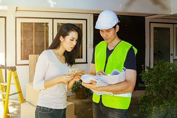 Mann berät Frau bezüglich Ihrer Renovierung und kosten der Fenster.